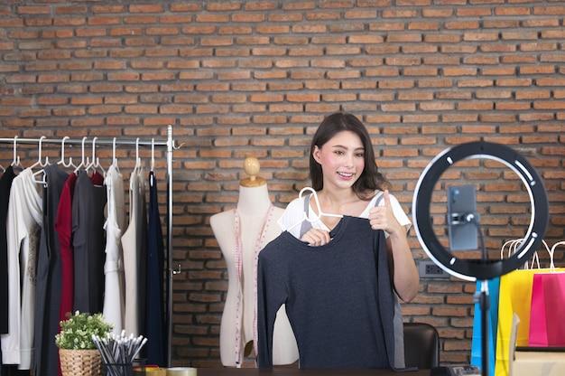 Asia bloggerin bewertung produkt und sprechende kamera live-aufnahme video in sozialen netzwerk zu hause, online-verkauf von kleidung in sozialen medien