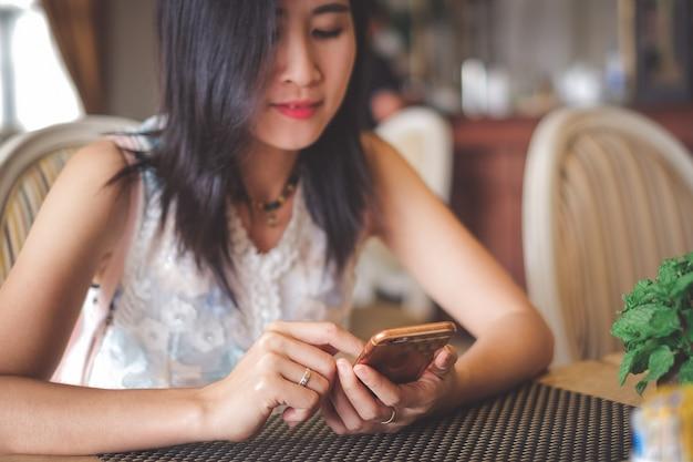 Asia-frau, die in der kaffeestube sitzt und handy für das überprüfen von social media verwendet