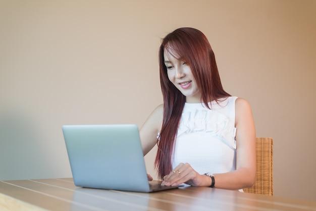 Asia-frau mit dem laptop, der am tisch sitzt