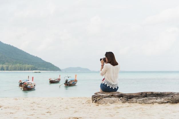 Asia mädchen sitzen und foto am strand machen