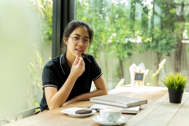 Asiam studentin, die kuchen mit buch und laptop in der kaffeestube isst.