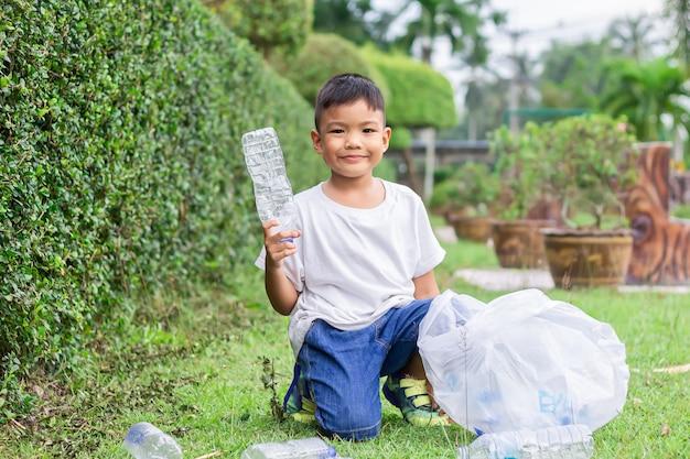 Asian child boy ist ein freiwilliger für die reinigung des feldbodens. er hob viele plastikflaschen und stroh auf dem boden auf.