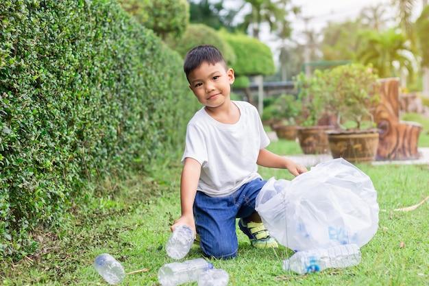 Asian child boy ist ein freiwilliger für die reinigung des feldbodens.