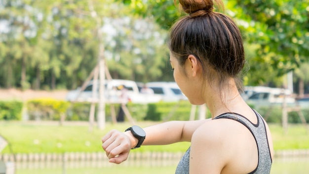 Asian cute gesunde passform und feste schlanke teen lady schauen auf die smartwatch, um gps einzustellen