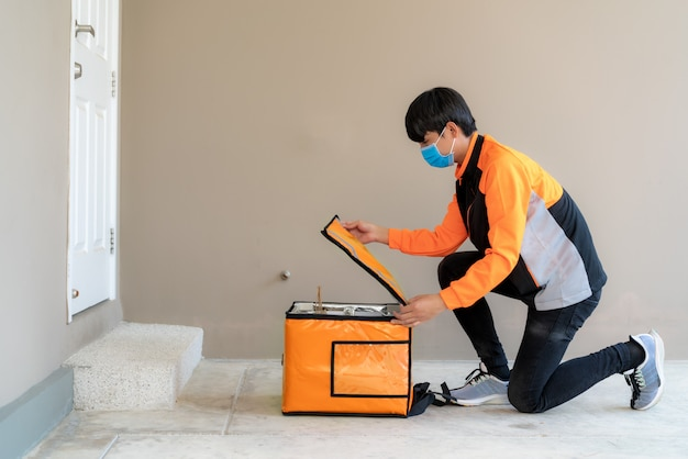 Asian delivery man drop und open delivery food box für kontaktlose oder kontaktfreie im vorhaus für soziale distanzierung für infektionsrisiko.