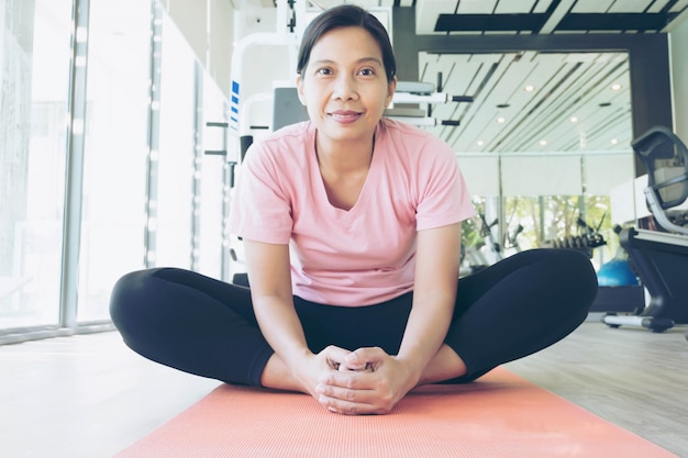 Asian fitness woman warm up vor dem training im fitnessstudio, frau mittleren alters, die yoga trainiert