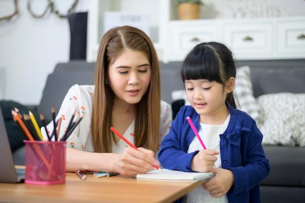 Asian happy mutter und tochter nutzen laptop, um zu hause online über das internet zu lernen. e-learning-konzept während der quarantänezeit.