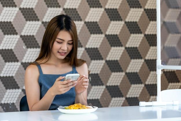 Asian influencer food blogger machen foto in neuen normalen restaurant