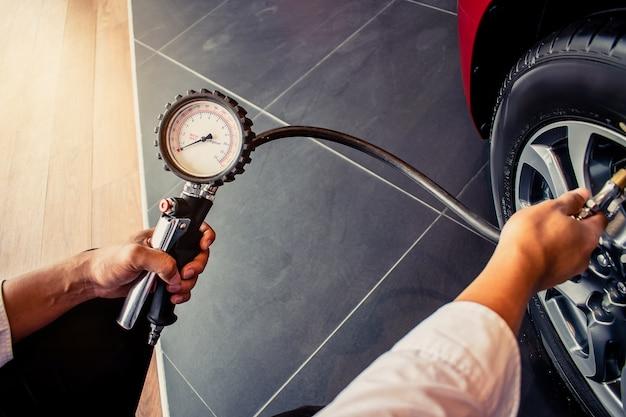 Asian man auto inspection messen sie menge aufgeblasene gummireifen