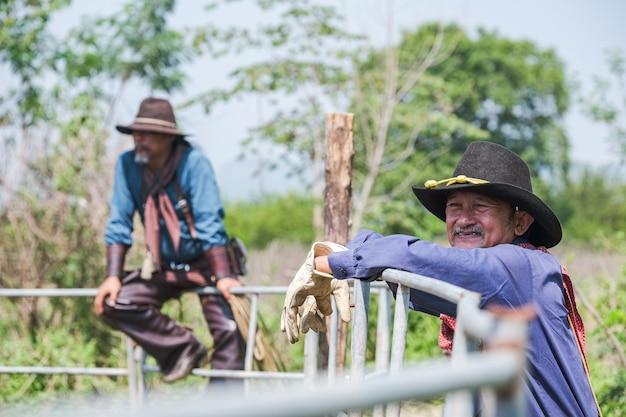 Asian man cowboy steht da, um die kuh als marke auf der ranch zu beobachten
