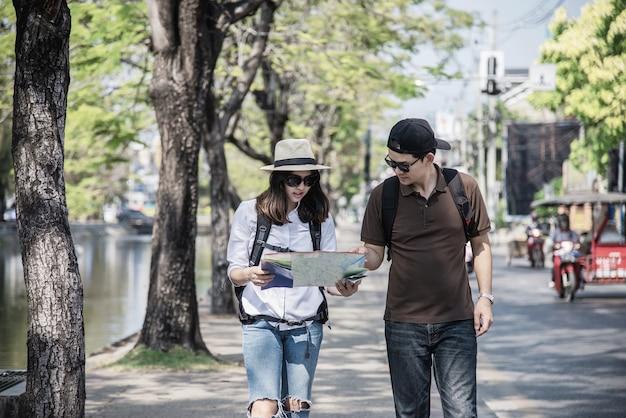Asiancouple-tourist, der den stadtplan kreuzt die straße hält
