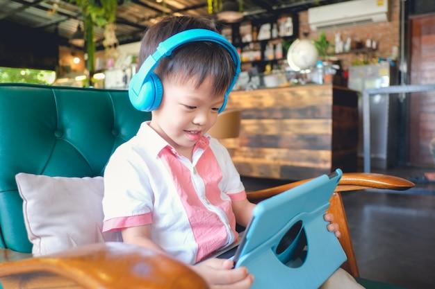 Asiat 3 - 4 jahre alte lächelnde kleinkindjungenkind beim sitzen im lehnsessel unter verwendung des tabletten-pc-computers
