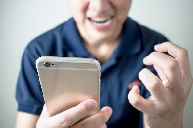 Asiaten ärgern sich über die nachricht auf dem smartphone im zimmer.