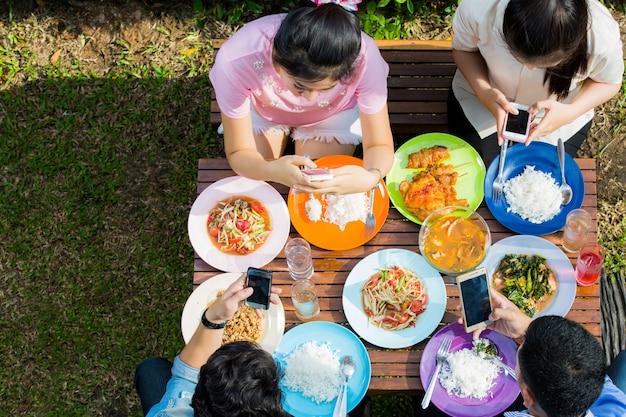 Asiaten essen im urlaub, jeder nimmt das telefon zum essen auf