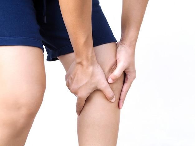 Asiaten haben knieschmerzen, beinschmerzen verwenden hände, die die beinmassage berühren, um muskeln zu entspannen und schmerzen zu lindern.