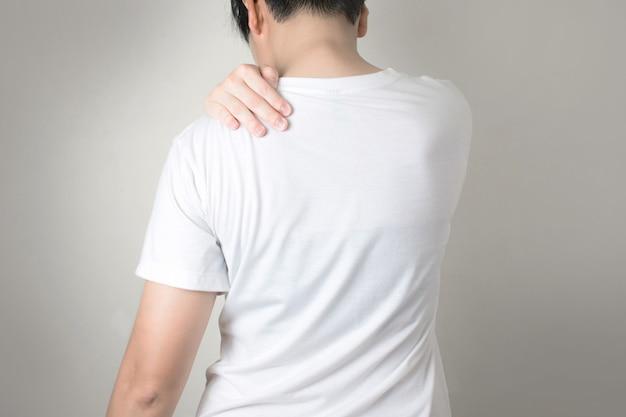 Asiaten haben schulterschmerzen. mit dem griff an der schulter.