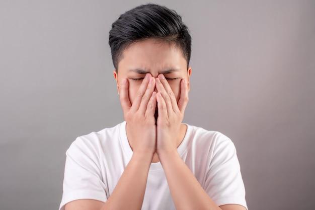 Asiaten mit kopfschmerzen und augen verwenden sie ihre hand, um es auf dem grau zu verstecken