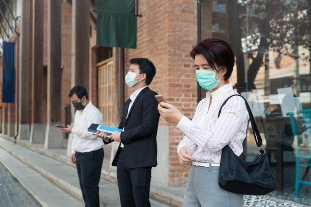 Asiaten tragen eine maske und halten soziale distanz, um die verbreitung von covid-19 zu vermeiden
