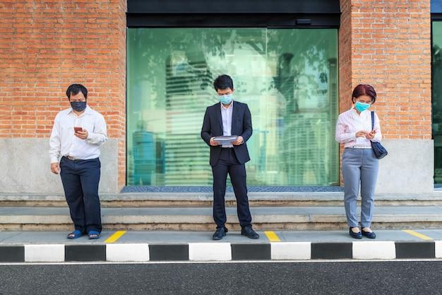 Asiaten tragen maske und halten soziale distanz