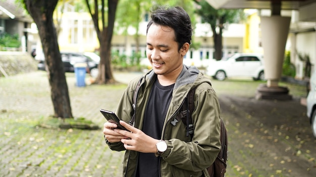 Asiaten tragen rucksäcke, während sie handy halten