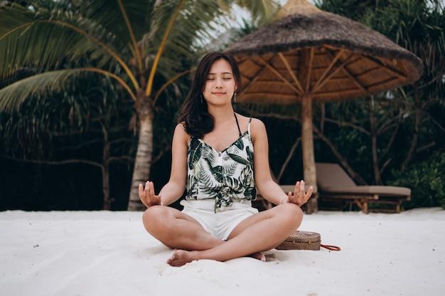 Asiatin am übenden yoga des strandes
