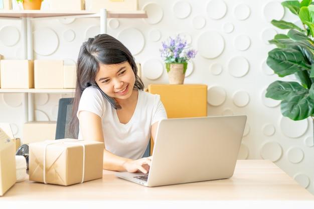 Asiatin amüsieren sich beim verwenden des internets auf laptop und telefon im büro