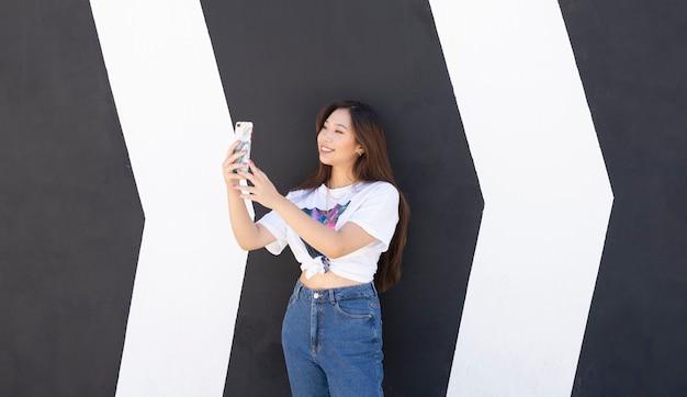 Asiatin an einer wand mit einem smartphone