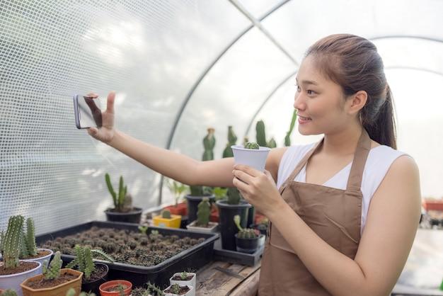 Asiatin arbeitet gerne mit kakteen und ist inhaberin eines start-up-unternehmens, das bäume online verkauft.