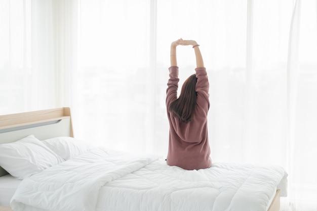 Asiatin auf dem bett und am morgen aufwachen