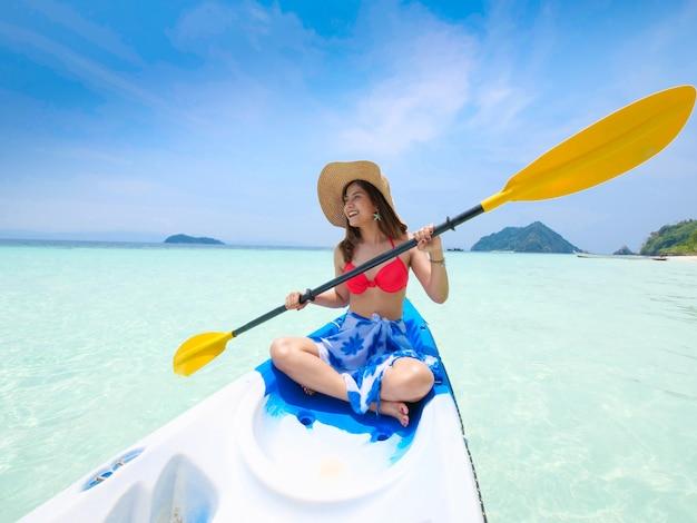 Asiatin auf dem kajakboot in blauem hintergrund andamans see und des blauen himmels