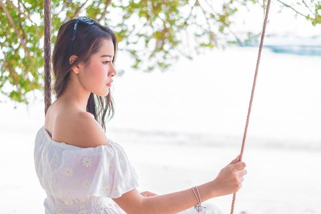 Asiatin auf dem weißen kleid, das auf schwingen am strand sitzt