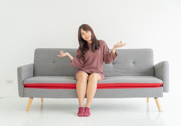 Asiatin auf sofa im wohnzimmer mit kopienraum