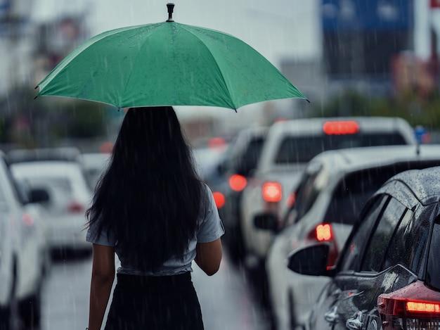 Asiatin benutzt den regenschirm, während es regnet. sie geht über die straße