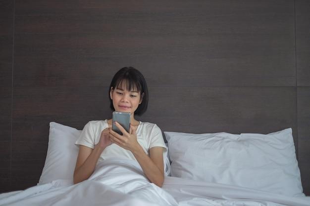 Asiatin benutzt smartphone glücklich aussehenden bildschirm und sitzt im weißen bett zu hause