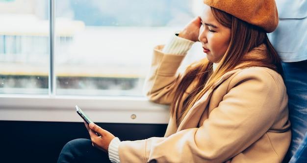 Asiatin benutzt smartphone im zug und reist in japan