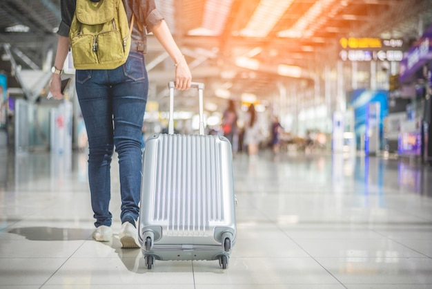 Asiatin der schönheit, die koffer im flughafen reist und hält. menschen und lebensstile