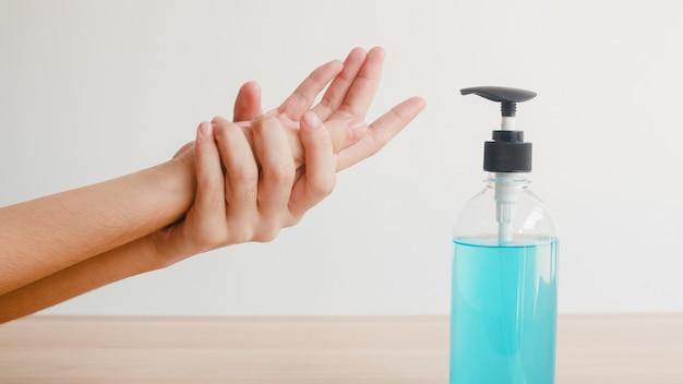 Asiatin, die alkohol-gel-händedesinfektionsmittel verwendet, waschen hand zum schutz des coronavirus. frau drückt alkoholflasche, um die hand für hygiene zu reinigen, wenn soziale distanzierung zu hause bleibt und selbstquarantänezeit.