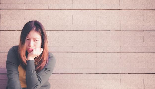 Asiatin, die allein und niedergedrückt, porträt der müden jungen frau, krise sitzt