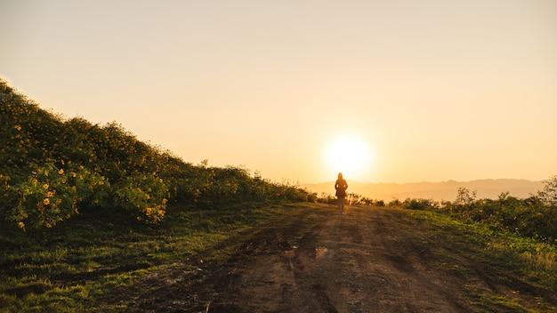 Asiatin, die alleine mit sonnenuntergang- und blumenfeldern steht.