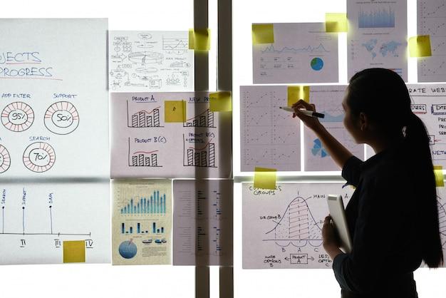 Asiatin, die am fenster im büro steht und ausdrucke mit geschäftsdiagrammen auf glas betrachtet