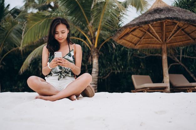 Asiatin, die am strand sitzt und telefon verwendet