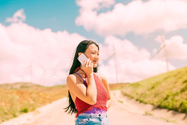 Asiatin, die am telefon in der landschaft spricht