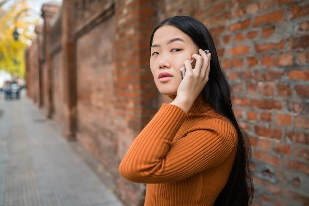 Asiatin, die am telefon spricht.