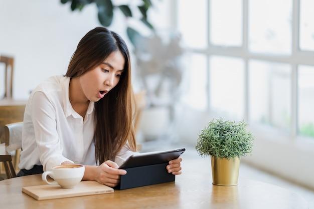 Asiatin, die an der kaffeestube sitzt