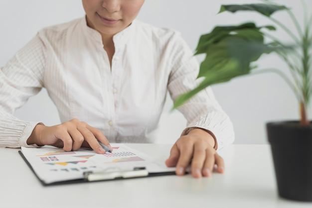 Asiatin, die an ihrem arbeitsplatz sitzt
