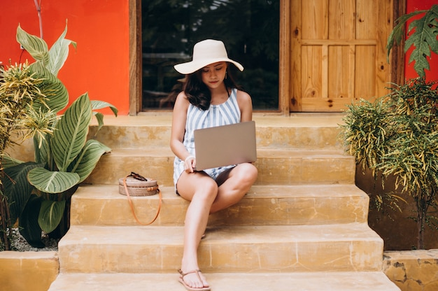 Asiatin, die an laptop auf ferien arbeitet und auf der treppe sitzt