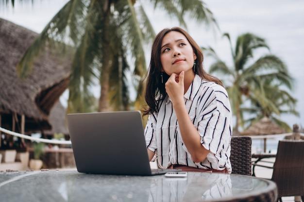 Asiatin, die an laptop auf ferien arbeitet