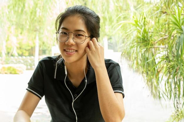 Asiatin, die an laptop mit dem kopfhörer betrachtet kamera arbeitet.
