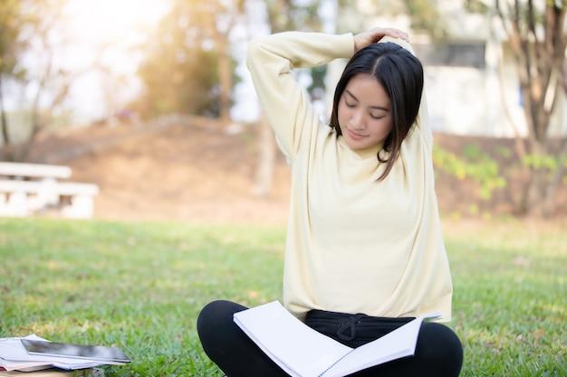 Asiatin, die auf das grüne gras nach lesebuch ausdehnt und sitzt und stark arbeitet