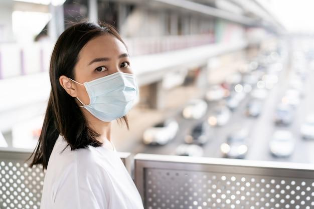 Asiatin, die auf der brücke in der stadt voll mit pm2.5 staub steht. frau, die schutzmaske trägt, um sich vor covid19 virus zu schützen. besorgnis der frau über die covid-19-krankheit. coronavirus-krise.